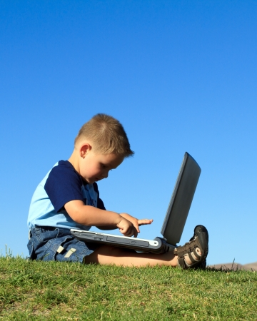 sitting down: little boy with laptop outdoors