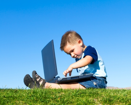 notebook: little boy with laptop outdoors