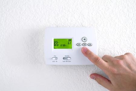 digitale thermostaat met de vinger te drukken op de knop Stockfoto