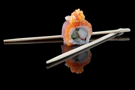 sushi with chopsticks over black background