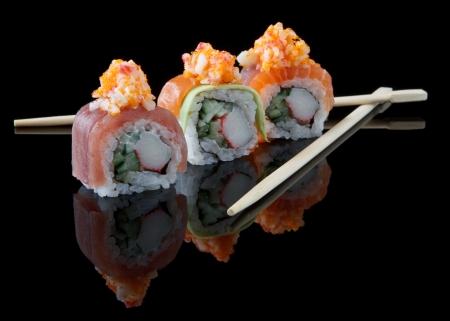 chopstick: sushi with chopsticks over black background