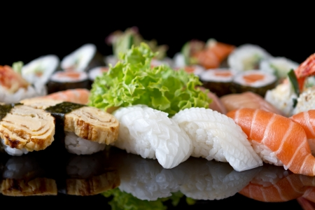japanese sake: sushi con la reflexión de cristal sobre fondo negro Foto de archivo