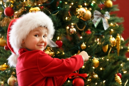 red christmas lights: boy decorating Christmas tree