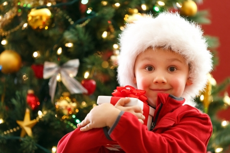 holding close: boy with Christmas gift