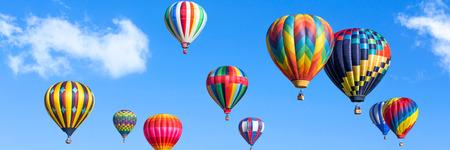 Kleurrijke heteluchtballonnen over blauwe hemel