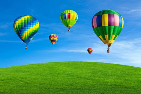 Hot air balloons flying over green field Фото со стока