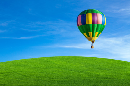 ballooning: Hot air balloon flying over green field Stock Photo