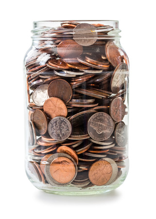 Jar full of coins isolated on white Stockfoto
