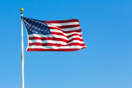 bandera estados unidos: Bandera de Estados Unidos contra el claro cielo azul Foto de archivo