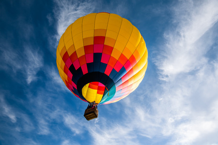 Hot air balloon against dark cloudy sky.