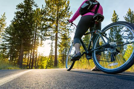 Biker on asphalt path at sunset