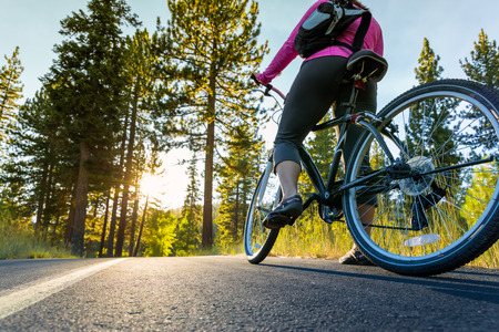 road cycling: Biker on asphalt path at sunset