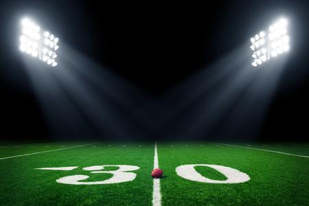 Campo de fútbol americano en la noche con las luces del estadio