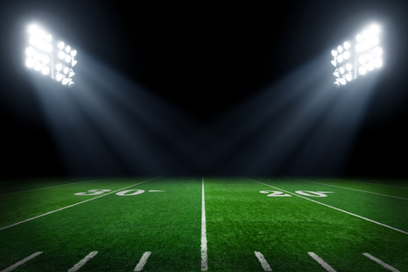 American football field at night with stadium lights Stock Photo