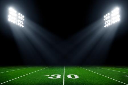 American football field at night with stadium lights 스톡 콘텐츠