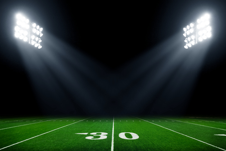 American football field at night with stadium lights Stok Fotoğraf