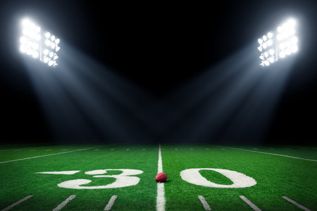 American football field at night with stadium lights Stockfoto