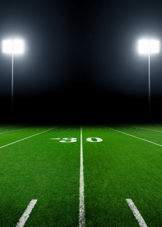 American football field at night with stadium lights Stock Photo