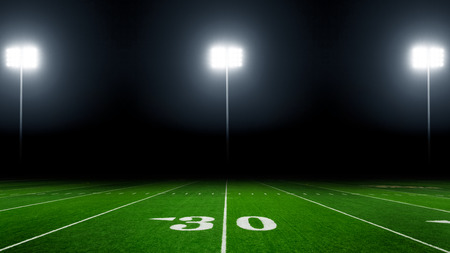 American football field at night with stadium lights 免版税图像