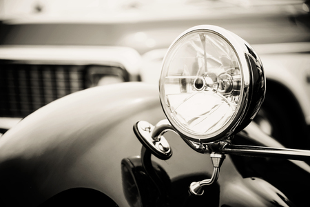 shiny black: Photograph of a classic vehicle with close-up on headlights.