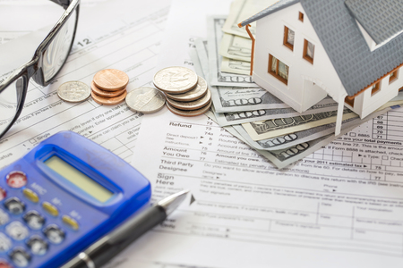 Miniature house with money on tax papers Stockfoto