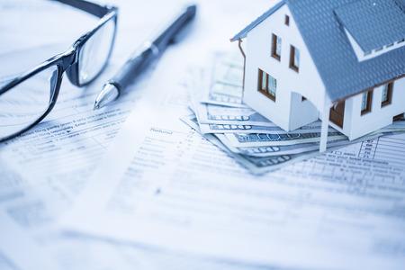 ingresos: Casa miniatura con el dinero en los papeles del impuesto Foto de archivo