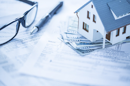 individual: Miniature house with money on tax papers Stock Photo