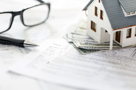 Miniature house with money on tax papers Archivio Fotografico