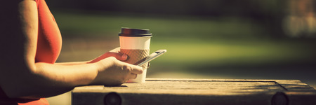 mobile sms: Woman at the park with take away coffee and smart phone