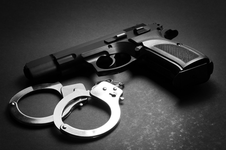 handgun with handcuffs over bark background Stock Photo