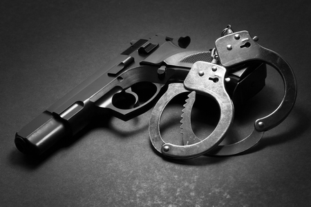 handgun with handcuffs over bark background Stock Photo
