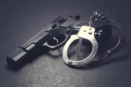 Handgun with handcuffs on dark background