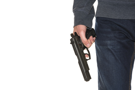 Armed person holding handgun wearing dark blue jeans and hoodie isolated on white background, copy space, close-up on gun