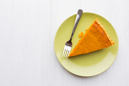 Slice of pumpkin pie photographed from above over white wooden background Reklamní fotografie