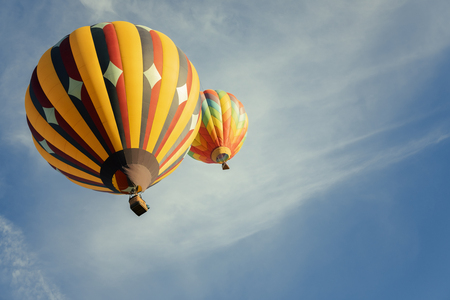 Multi colored hot air balloons flying over blue sky