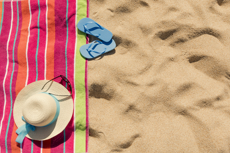 Beach towel with hat, sun glasses and flip flops on sand Фото со стока