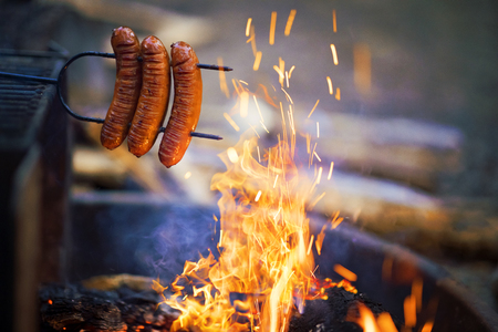 Preparing sausage on campfire, camping dinner