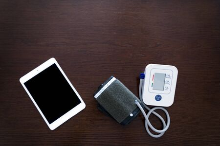 Digital blood pressure monitor with tablet on wooden table