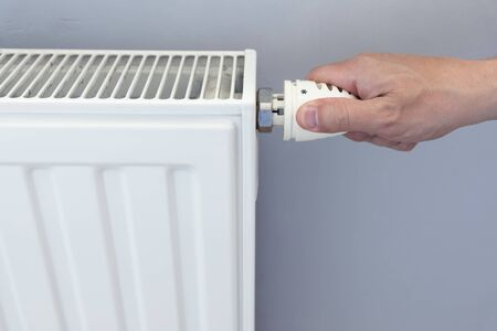 Hand adjusting heater valve of heating radiator in a room.