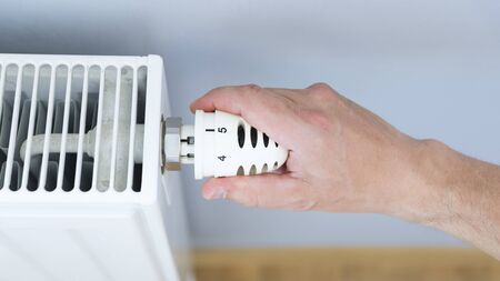 Hand adjusting thermostat valve of heating radiator in a room.