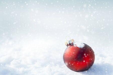 Palla di Natale rossa su sfondo bianco di neve Archivio Fotografico