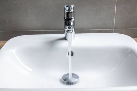 Bathroom faucet with running water into ceramic sink