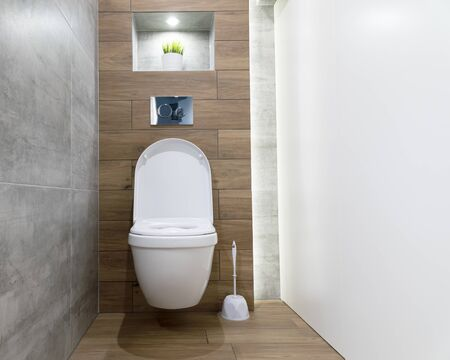 Modern bathroom interior, white ceramic toilet bowl on the wall with tiles