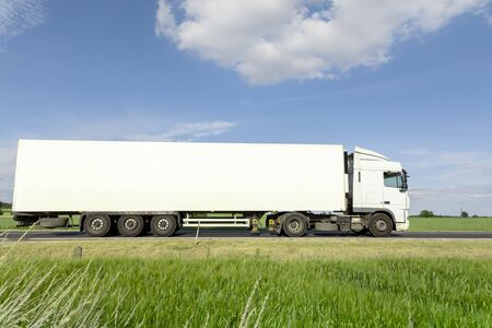 White transport truck driving on the road, green meadow with blue sky Reklamní fotografie