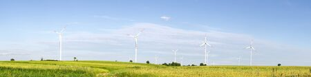 wind turbines in green field, countryside area with blue sky