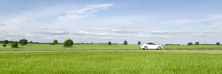 Small passenger car driving through green countryside meadow, blue sky