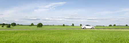 Small passenger car driving through green countryside meadow, blue sky Reklamní fotografie - 145318496