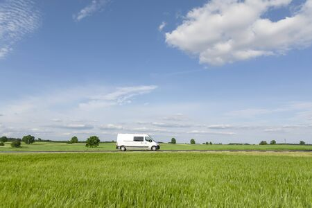Transport van driving on the road, green meadow with blue sky