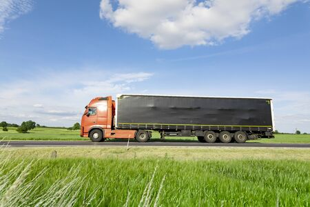 transport truck driving on the road, green meadow with blue sky