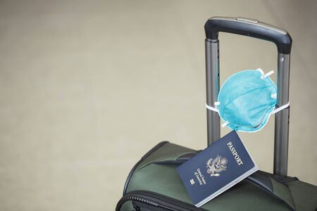 personal luggage with passport and flu virus mask to protect against coronavirus, global epidemic concept